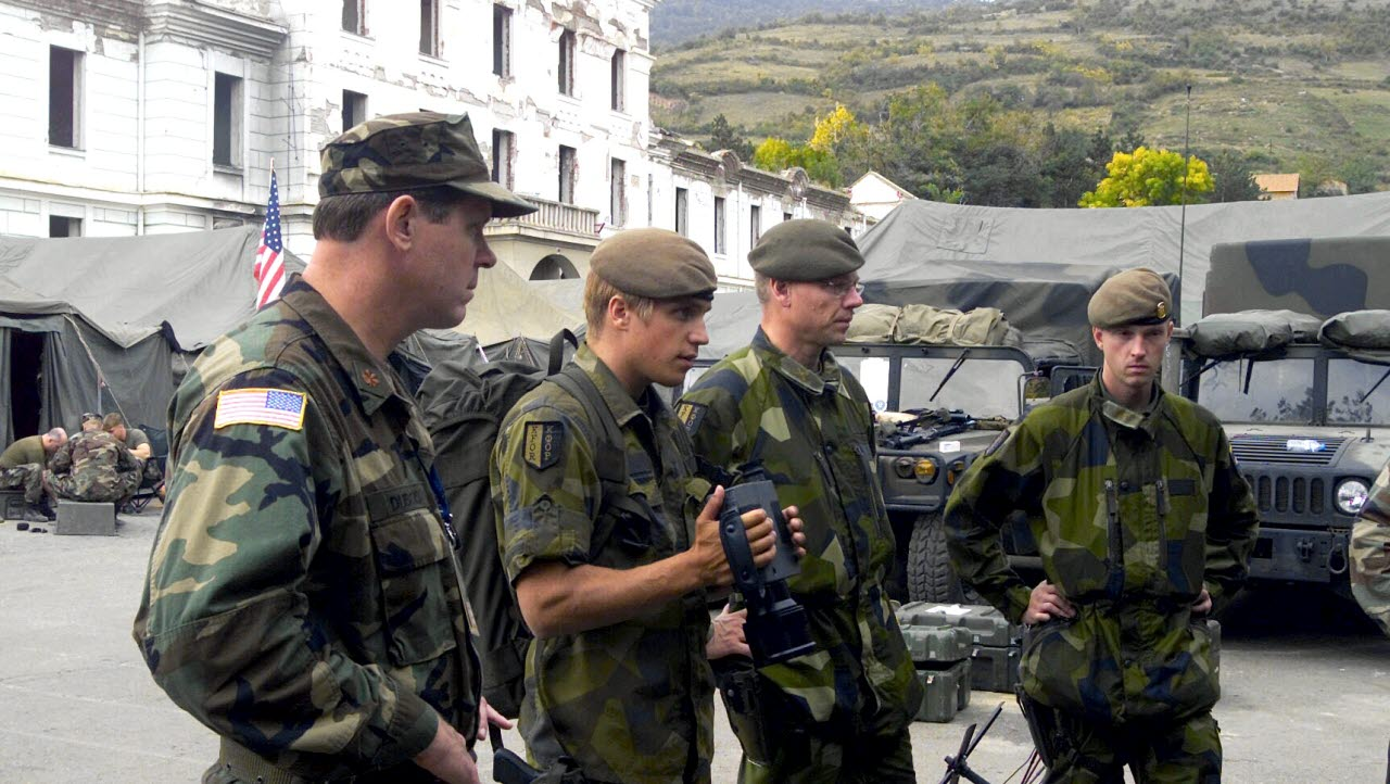 Swedish military soldiers working as a part of the Multinational Brigade South, studies a display of gear used by the Marine Liaison Element (MLE), 24th Marine Expeditionary Unit (MEU) as the Marines of the MLE explain the gear in Prizren, Kosovo during Operation DYNAMIC RESPONSE 2002.