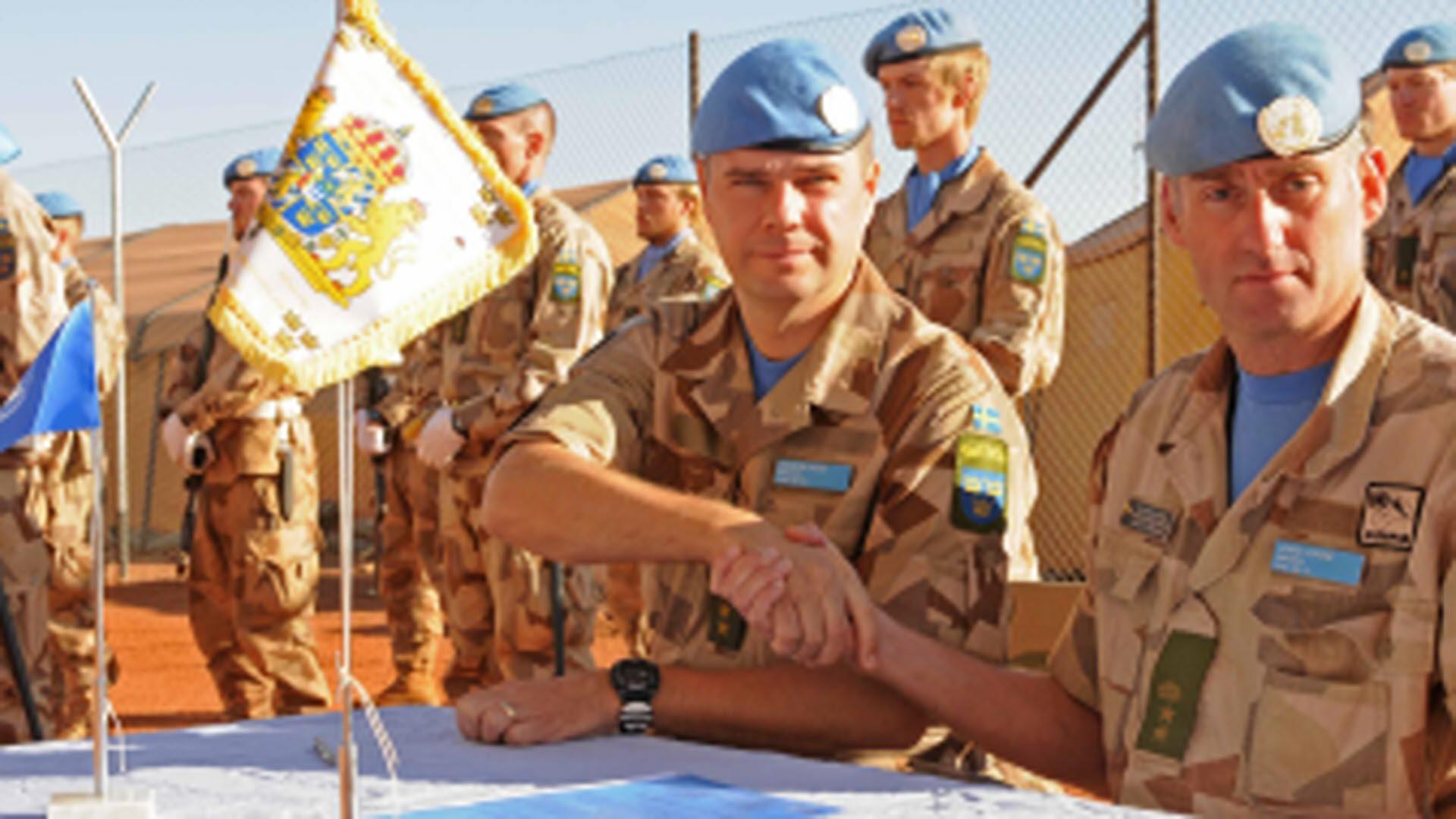 Två män i sandfärgade uniformer och blå baskrar sitter vid bord och tar  varandra formellt i 76adc7a441ca5